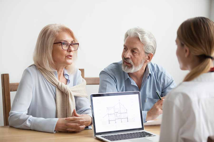 couple looking at home improvement ideas with designer on laptop
